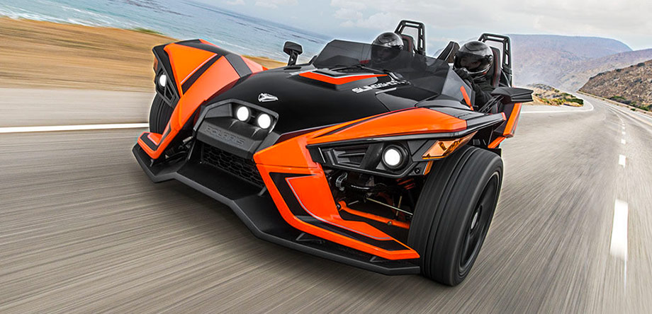 two people with helmets on a polaris slingshot coming out of an alley