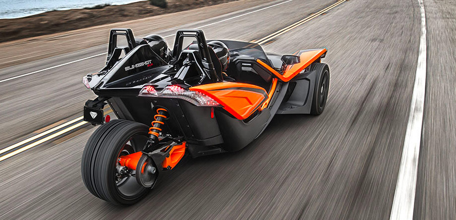 two poeple with helmets driving  a polaris slingshot on the street