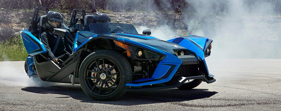 a man taking out his helmet and getting out from the polaris slingshot